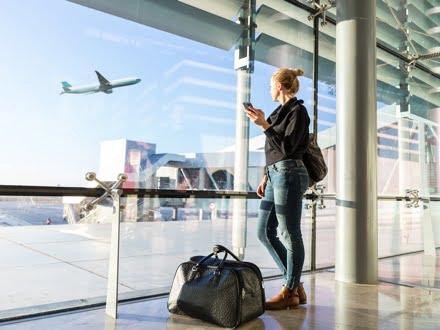 Young woman waiting at airport, looking through the gate window.Young woman waiting at airport, looking through the gate window.